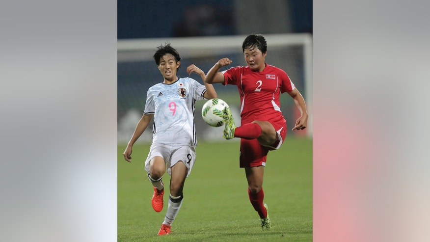 North Korea's Jon Yon Sim, right, fights for the ball against Japan's Riko Ueki during the FIFA U-17 women's World Cup final match in Amman Friday, Oct. 21, 2016. North Korea defeated Japan 5:4 in a penalty shootout and became champion. (AP Photo/Raad Adayleh)