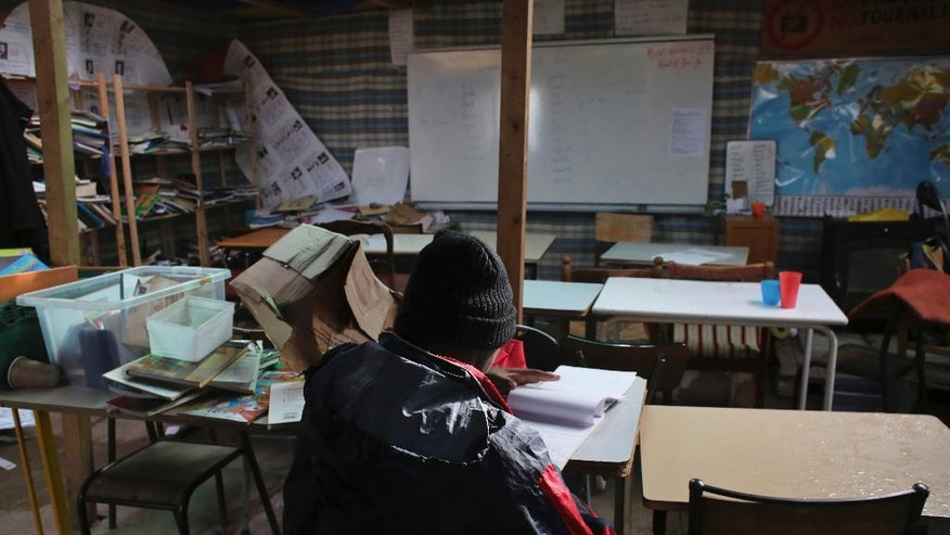 "A migrant studies in a school in a makeshift migrant camp near Calais, France, Saturday, Oct. 22, 2016. French authorities say the closure of the slum-like camp in Calais will start on Monday and will last approximately a week in what they describe as a ""humanitarian"" operation. (AP Photo/Thibault Camus)"