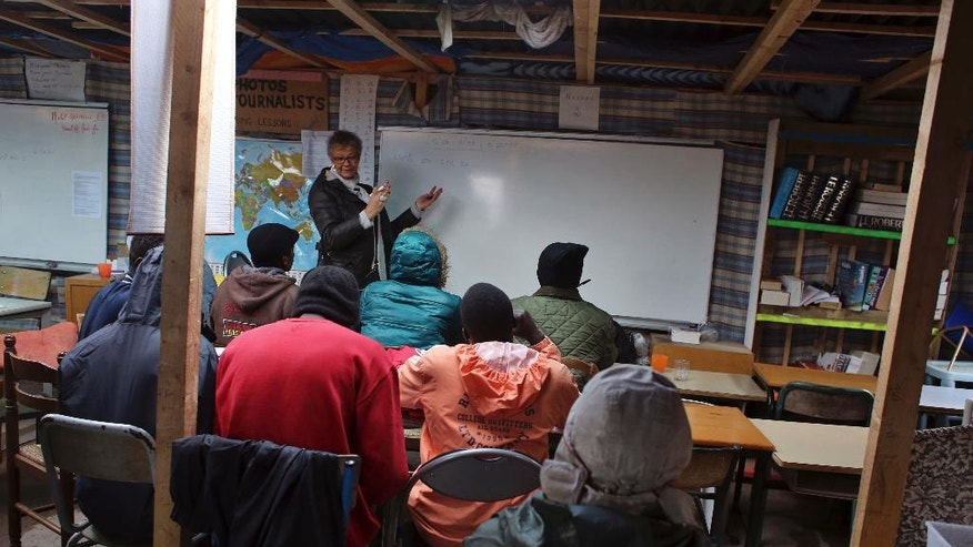 "Volunteer teacher Laurence teach French to migrants in a classroom at a makeshift migrant camp near Calais, France, Saturday, Oct. 22, 2016. French authorities say the closure of the slum-like camp in Calais will start on Monday and will last approximately a week in what they describe as a ""humanitarian"" operation. (AP Photo/Thibault Camus)"