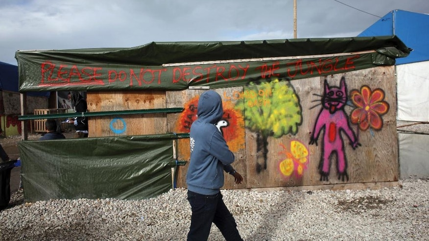 "A migrant walks past a restaurant where a banner reads ""Please do not destroy the jungle""  in a makeshift migrant camp near Calais, France, Saturday, Oct. 22, 2016. French authorities say the closure of the slum-like camp in Calais will start on Monday and will last approximatively a week in what they describe as a ""humanitarian"" operation. (AP Photo/Thibault Camus)"