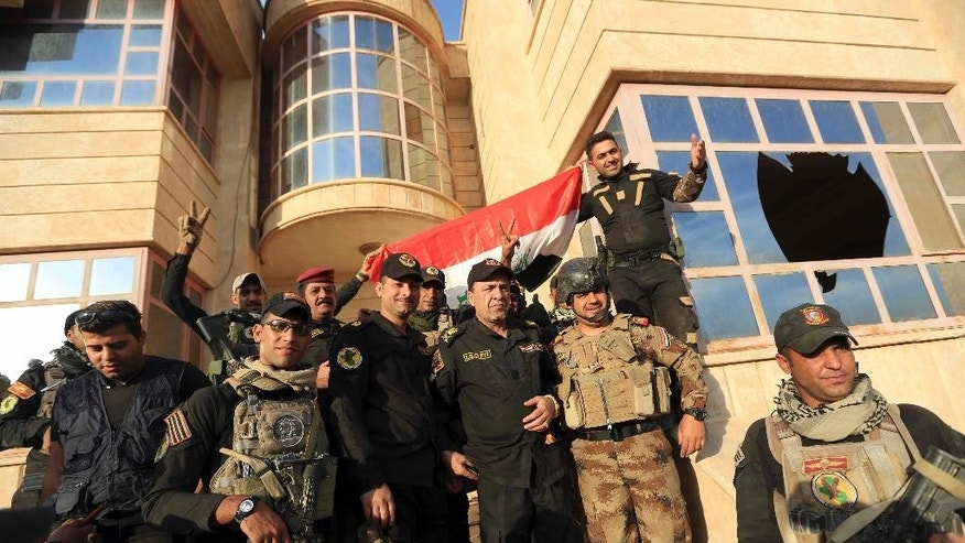 Iraq's elite counterterrorism force soldiers raise an Iraqi flag in front of the main church in Bartella, Iraq, Friday, Oct. 21, 2016. By Thursday, the Iraqi forces had advanced as far as Bartella, a historically Christian town some nine miles (15 kilometers) from Mosul's outskirts. (AP Photo/Khalid Mohammed)