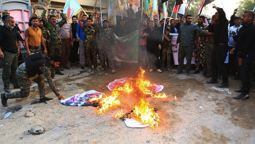 Iraqi protesters burn Turkish flags and Israeli flags during a demonstration calling for the withdrawal of Turkish troops from northern Iraq, in Basra, 340 miles (550 kilometers) southeast of Baghdad, Iraq on Saturday, Oct. 22, 2016.(AP Photo/Nabil al-Jurani)