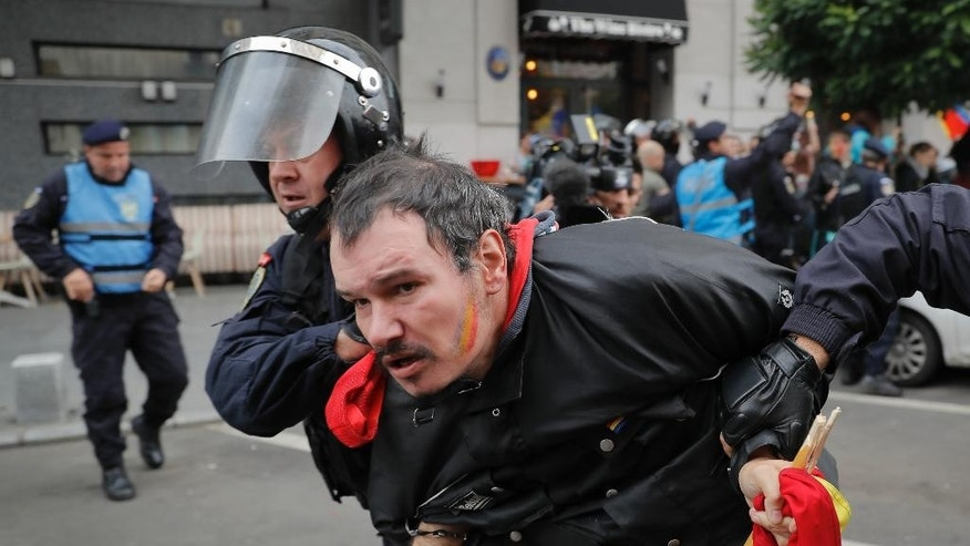 A man is detained by riot police after scuffles broke out during a rally demanding the reunification of Romania and Moldova, in Bucharest, Romania, Saturday, Oct. 22, 2016. More than 2,000 people have marched through the Romanian capital demanding that their country reunites with neighboring Moldova and blocked traffic on a main boulevard in the Romanian capital after scuffles with riot police. (AP Photo/Vadim Ghirda)