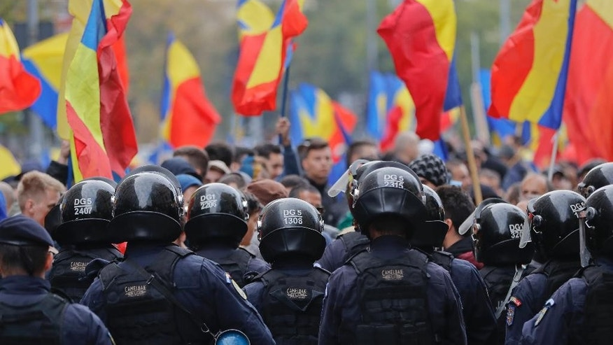 Riot police blocks protesters after scuffles broke during a rally demanding the reunification of Romania and Moldova, in Bucharest, Romania, Saturday, Oct. 22, 2016. More than 2,000 people have marched through the Romanian capital demanding that their country reunites with neighboring Moldova and blocked traffic on a main boulevard in the Romanian capital after scuffles with riot police. (AP Photo/Vadim Ghirda)