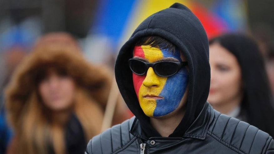 A man with his face painted in the Romanian and Moldovan flag colors, attends a rally demanding the reunification of Romania and Moldova, in Bucharest, Romania, Saturday, Oct. 22, 2016. More than 2,000 people have marched through the Romanian capital demanding that their country reunites with neighboring Moldova and blocked traffic on a main boulevard in the Romanian capital after scuffles with riot police. (AP Photo/Vadim Ghirda)