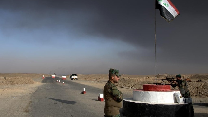 Iraqi troops guards a checkpoint near the village of Awsaja, Iraq, as smoke from fires lit by Islamic State militants at oil wells and a sulfur plant fills the air on Saturday, Oct. 22, 2016.   U.S. military officials say that a fire at the sulfur plant in northern Iraq is creating a potential breathing hazard for American forces and other troops at a logistical base south of Mosul.  (AP Photo/Adam Schreck)