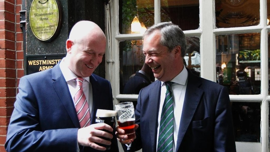 FILE - In this Monday, May 26, 2014 file photo, Nigel Farage, the then leader of the UK Independence Party and newly elected MEP, right, enjoys a pint of beer with UKIP deputy leader and MEP, Paul Nuttall at a pub before his post European Elections press conference in central London. Two prominent candidates have announced they are running for leadership of Britain's fractious right-wing U.K. Independence Party _ both warning UKIP faces extinction if it doesn't change. Suzanne Evans and Paul Nuttall declared their candidatures on Sunday Oct. 23, 2016.  (AP Photo/Sang Tan, File)