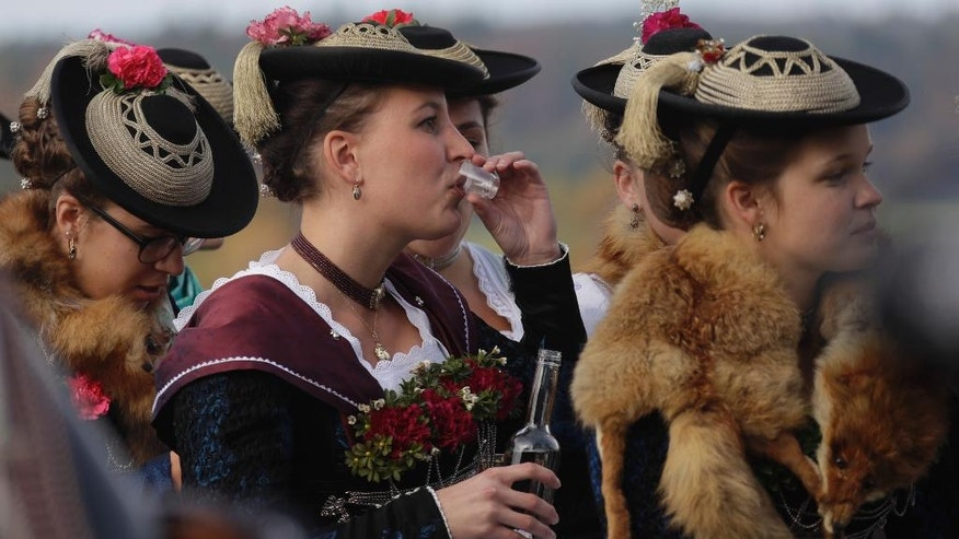 A young woman in her costume of the region drinks liqueur during the traditional Leonhardi pilgrimage in Warngau near Munich, Germany, Sunday, Oct. 23, 2016. The annual pilgrimage honors St. Leonhard, patron saint of the highland farmers for horses and livestock. (AP Photo/Matthias Schrader)