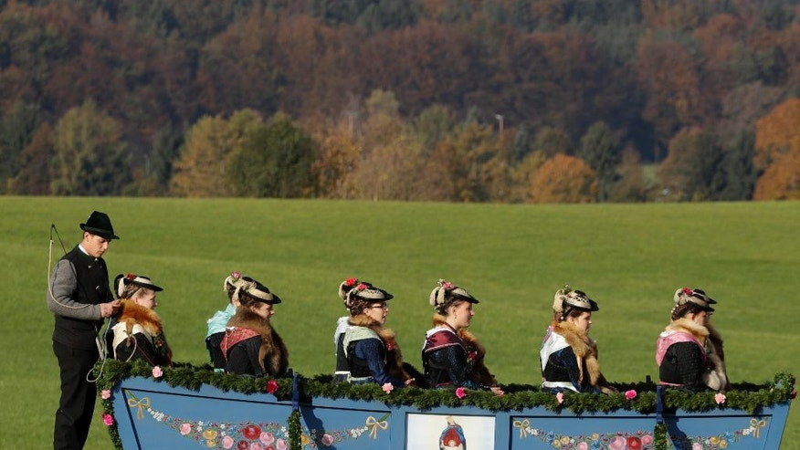Women in their costumes of the region sit in a horse-drawn carriage during the traditional Leonhardi pilgrimage in Warngau near Munich, Germany, Sunday, Oct. 23, 2016. The annual pilgrimage honors St. Leonhard, patron saint of the highland farmers for horses and livestock. (AP Photo/Matthias Schrader)