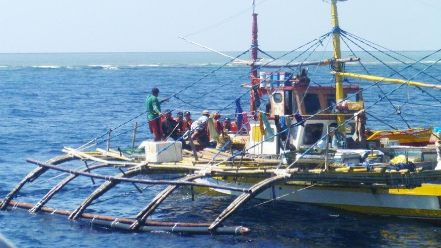 FILE - In this Sept. 23, 2015, file photo provided by Renato Etac, Chinese Coast Guard members, wearing black caps and orange life vests, approach Filipino fishermen as they confront them off Scarborough Shoal at South China Sea in northwestern Philippines. Philippine President Rodrigo Duterte said Sunday, Oct. 23, 2016, Filipino fishermen may be able to return to the China-held Scarborough Shoal in a few days after he discussed the territorial rift with Chinese leaders during his trip to Beijing this past week. (Renato Etac via AP, File)