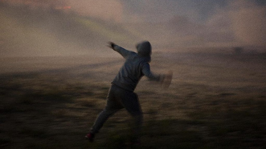 "A demonstrator throws stones toward French riot police officers during clashes in a makeshift migrant camp near Calais, northern France, on Saturday, Oct. 22, 2016. French authorities say the closure of the slum-like camp in Calais will start on Monday and will last approximately a week in what they describe as a ""humanitarian"" operation. (AP Photo/Emilio Morenatti)"