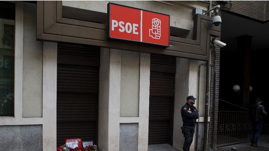 Red roses, a Spanish socialist symbol, lie outside the socialist headquarters as a protest gesture while a police officer stands guard in Madrid, Spain, Saturday, Oct. 22, 2016. Spain's socialist party will meet Sunday to decide if they will abstain in a parliamentary vote to let acting conservative Prime Minister Mariano Rajoy's build a minority government and end a nine-month political deadlock but many socialist voters are not in agreement. 'Messages by the roses read in Spanish 'We want to decide' and 'No is no'. (AP Photo/Paul White)