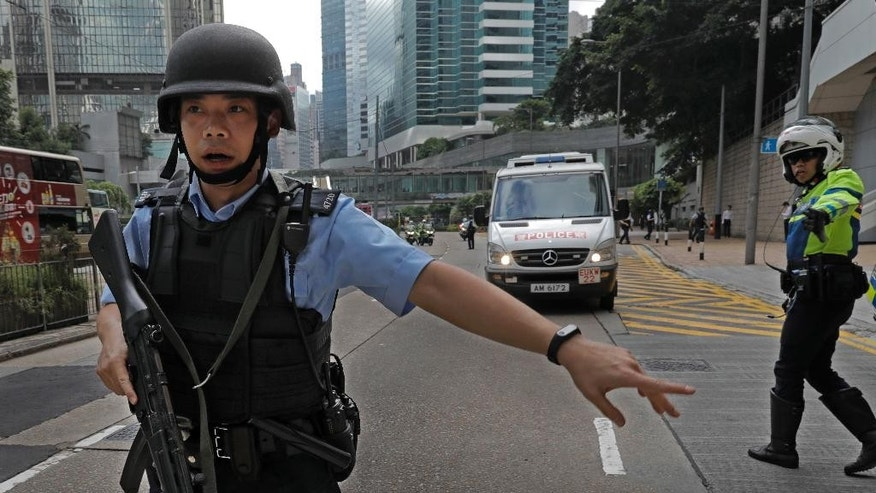 A police officer holds a machine gun trying to make way of a prison bus which carries British banker Rurik Jutting upon his arrival at the High Court in Hong Kong, Monday, Oct. 24, 2016. Jutting accused of the grisly 2014 killings of two Indonesian women pleaded not guilty when he went on trial Monday, in a case expected to highlight the Asian financial hub's inequality and privileged lifestyle of its wealthy expat elite. (AP Photo/Vincent Yu)