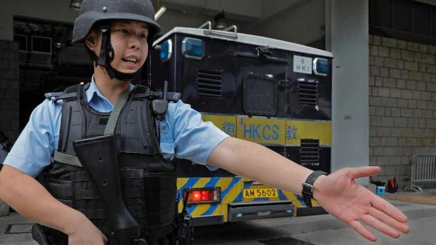 A police officer holds a machine gun trying to make way of a prison bus carrying British banker Rurik Jutting upon arrival at the High Court in Hong Kong, Monday, Oct. 24, 2016. Jutting accused of the grisly 2014 killings of two Indonesian women pleaded not guilty when he went on trial Monday, in a case expected to highlight the Asian financial hub's inequality and privileged lifestyle of its wealthy expat elite. (AP Photo/Vincent Yu)