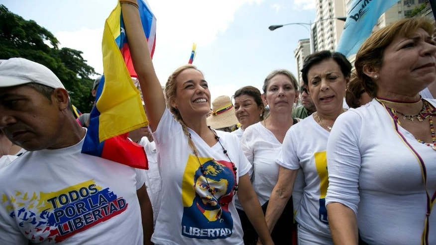 Women protest to demand a recall referendum against Venezuela's President Nicolas Maduro, as they march along a main street in Caracas, Venezuela, Saturday, Oct. 22, 2016. Venezuela is bracing for turbulence after the government blocked a presidential recall referendum in a move opposition leaders are calling a coup. The march was led by the wives of jailed activists. (AP Photo/Ariana Cubillos)