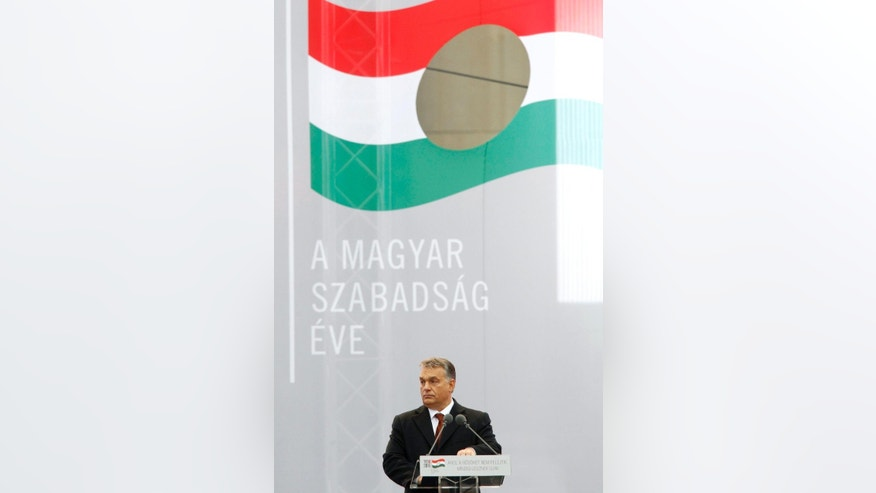 Hungarian Prime Minister Viktor Orban delivers his address during the state commemoration ceremony of the 1956 Hungarian revolution and freedom fight against communism and Soviet rule in front of the Parliament building in downtown Budapest, Hungary, Sunday, Oct. 23, 2016, on the 60th anniversary of the outbreak of the uprising.  Banner erads: The Year if Hungarian Freedom. (Zsolt Szigetvary/MTI via AP)