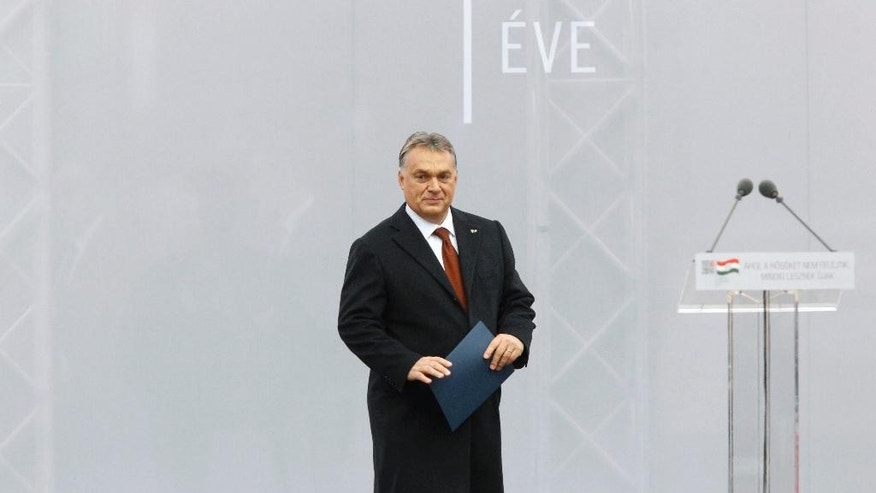 Hungarian Prime Minister Viktor Orban steps on the podium to deliver his address during the state commemoration ceremony of the 1956 Hungarian revolution and freedom fight against communism and Soviet rule in front of the Parliament building in downtown Budapest, Hungary, Sunday, Oct. 23, 2016, on the 60th anniversary of the outbreak of the uprising. (Zsolt Szigetvary/MTI via AP)