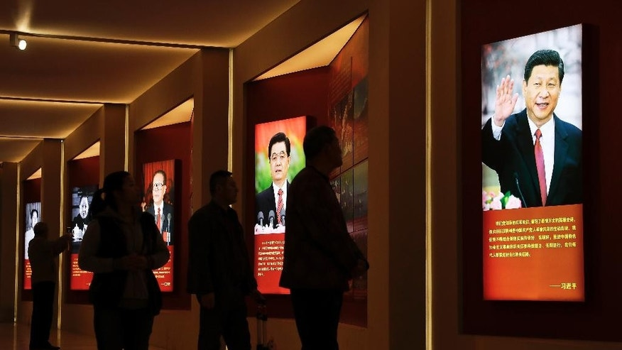 Visitors walk past images of China's past and present leaders, from left, Mao Zedong, Deng Xiaoping, Jiang Zemin, Hu Jintao and Xi Jinping on display at an exhibition on the Long March at the military museum in Beijing, Monday, Oct. 24, 2016. Having punished more than a million Communist Party members for corruption, current President Xi will use a key meeting that started Monday to drive home the message that his signature anti-graft campaign is far from over and that his authority remains undiminished. (AP Photo/Andy Wong)