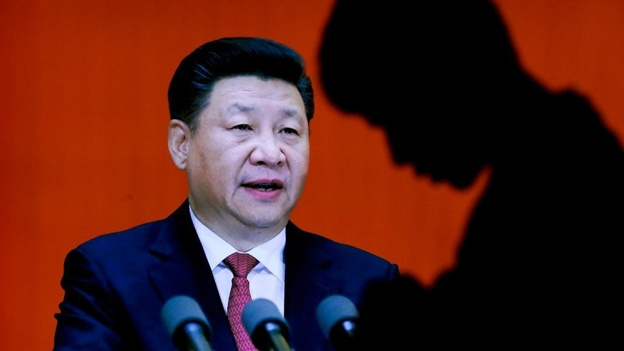 A man walks past an image of Chinese President Xi Jinping on display at an exhibition on the Long March at the military museum in Beijing, Monday, Oct. 24, 2016. Having punished more than a million Communist Party members for corruption, Chinese President Xi Jinping will use a key meeting that started Monday to drive home the message that his signature anti-graft campaign is far from over and that his authority remains undiminished. (AP Photo/Andy Wong)