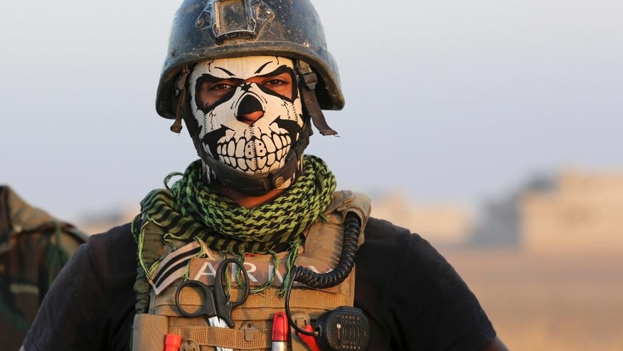 FILE -- In this Thursday, Oct. 20, 2016 file photo a member of Iraq's elite counterterrorism forces pauses as they advance towards the city of Mosul, Iraq. In the week since Iraq launched an operation to retake Mosul from the Islamic State group, its forces have pushed toward the city from the north, east and south, battling the militants in a belt of mostly uninhabited towns and villages. In the heavily mined approaches to the city they met with fierce resistance, as IS unleashed suicide truck bombs, rockets and mortars. (AP Photo/Khalid Mohammed, File)