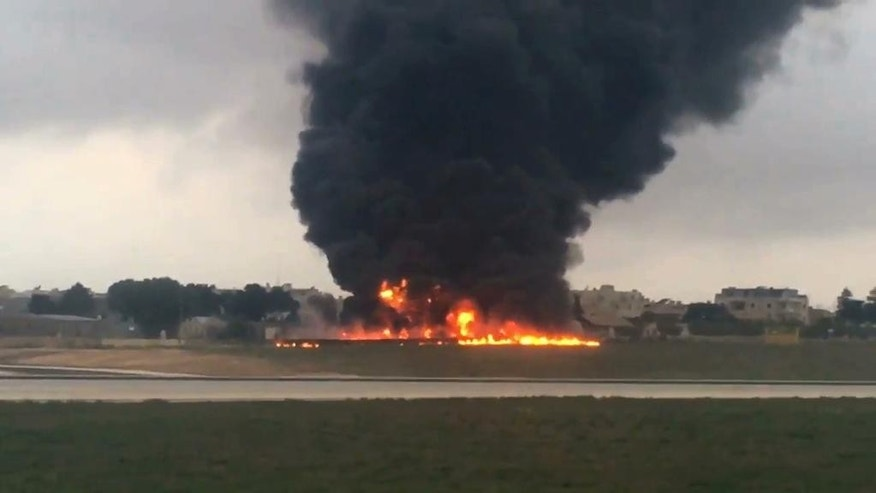 In this image taken from a video smoke billows as a light plane crashed after takeoff from Malta airport, in Valletta, Monday, Oct. 24, 2016. Officials say a light plane has crashed after takeoff from Malta International Airport, killing all five people on board. The twin-prop Metroliner tipped toward the right and crashed into the ground soon after lifting off at 7:20 a.m. Monday, bursting into flames, eyewitnesses said. (AP Photo/Ed De Gaetano)