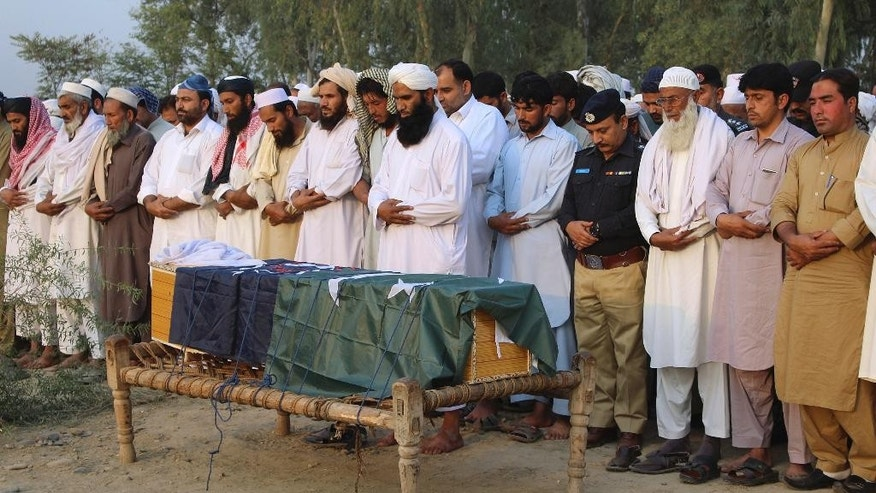 Local residents offer the funeral prayer of an intelligence officer in Charsadda, Pakistan, Monday, Oct. 24, 2016. Police officer Khalid Khan says two gunmen on a motorcycle opened fire early on Monday, killing intelligence officer Akbar Ali in the Charsadda district of Khyber Pakhtunkhwa province. Khan says the attackers fled the scene. (AP Photo/Zia Muhammad)