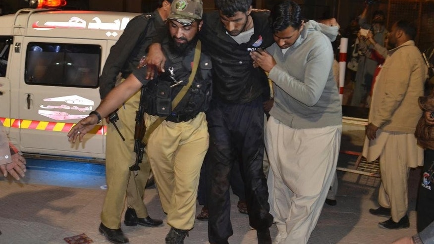 A Pakistani volunteer and a police officer rush an injured person to a hospital in Quetta, Pakistan, Monday, Oct. 24, 2016. A government official said tens of police trainees were killed when gunmen attacked a hostel at a police training center in Pakistan's restive southwestern Baluchistan province. (AP Photo/Arshad Butt)