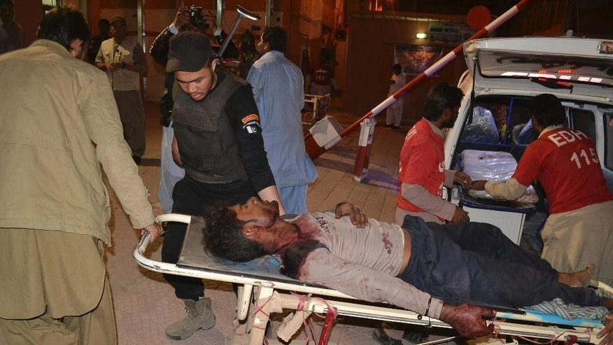 Pakistani volunteers rush an injured person to a hospital in Quetta, Pakistan, Monday, Oct. 24, 2016. A government official said tens of police trainees were killed when gunmen attacked a hostel at a police training center in Pakistan's restive southwestern Baluchistan province. (AP Photo/Arshad Butt)