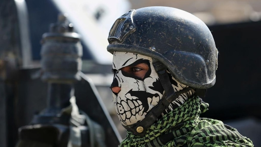 A member of Iraq's elite counterterrorism forces stands guard in the town of Bartella, Iraq, Sunday, Oct. 23, 2016. Iraqi forces captured Bartella, around 15 kilometers (9 miles) east of Mosul. (AP Photo/Khalid Mohammed)