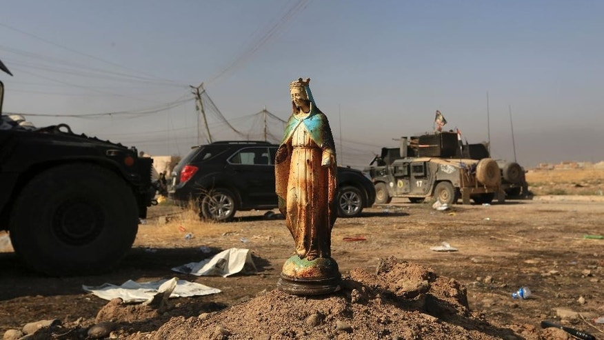 A statue of Virgin Mary is placed in a street in Bartella, Iraq, Sunday, Oct. 23, 2016. Iraqi forces captured Bartella, around 15 kilometers (9 miles) east of Mosul. (AP Photo/Khalid Mohammed)