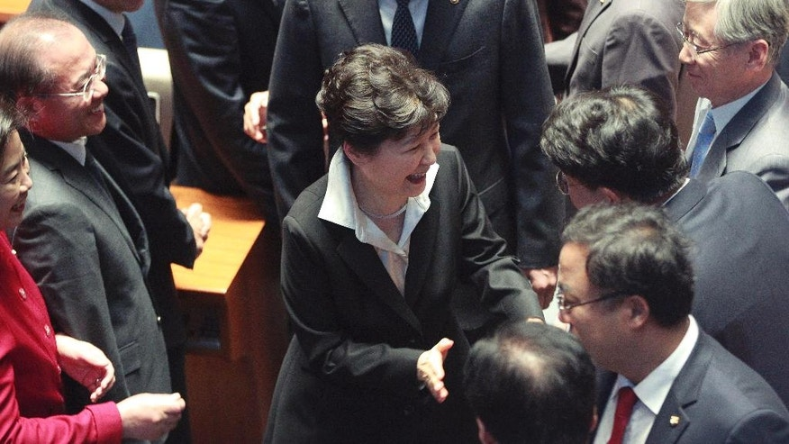 South Korean President Park Geun-hye, center, is greeted by lawmakers after delivering a speech at the National Assembly in Seoul, South Korea, Monday, Oct. 24, 2016. Park proposed revising the country's Constitution to change the current single five-year presidential system. Critics quickly criticized Park's overture, saying it appears aimed at diverting public attention away from a snowballing corruption scandal involving a purported longtime confidant of hers. (AP Photo/Ahn Young-joon)