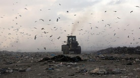 In this Wednesday, Oct. 19, 2016 photo, birds fly over a bulldozer working on a mound of garbage on the outskirts of Gaza City. In the struggling Gaza Strip, Omar Ramlawi's plastic factory is one of the few businesses that has managed to stay afloat, overcoming dire shortages of raw materials by resorting to an unusual source: recycling. Recycling has never been a priority in Gaza, a crowded and impoverished seaside territory whose already weak economy has been devastated by years of conflict with Israel and mismanagement by the ruling Islamic militant Hamas movement. (AP Photo/ Khalil Hamra)