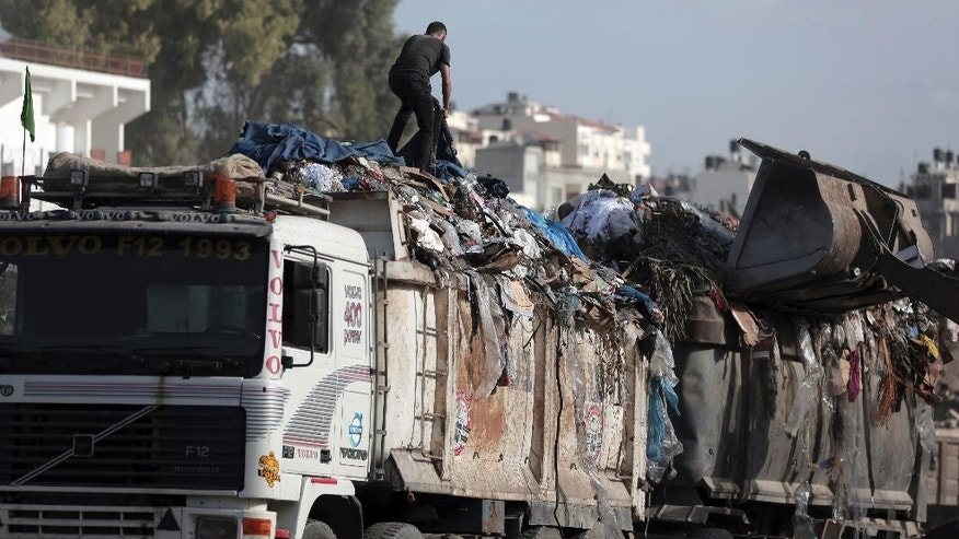 In this Wednesday, Oct. 19, 2016 photo, a Palestinian works loading a truck with garbage in Gaza City. In the struggling Gaza Strip, Omar Ramlawi's plastic factory is one of the few businesses that has managed to stay afloat, overcoming dire shortages of raw materials by resorting to an unusual source: recycling. Recycling has never been a priority in Gaza, a crowded and impoverished seaside territory whose already weak economy has been devastated by years of conflict with Israel and mismanagement by the ruling Islamic militant Hamas movement. (AP Photo/ Khalil Hamra)