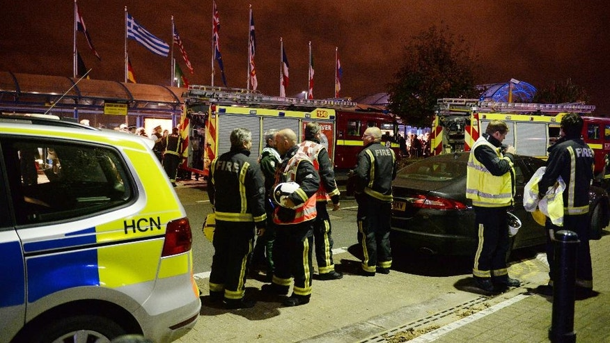 """Emergency services outside London City Airport after people were evacuated after what the emergency services called a reported """"chemical incident."""", Friday, Oct. 21, 2016. London Fire Brigade says City Airport has been declared safe, three hours after it was evacuated by a suspected chemical incident. (Victoria Jones/PA via AP)"""