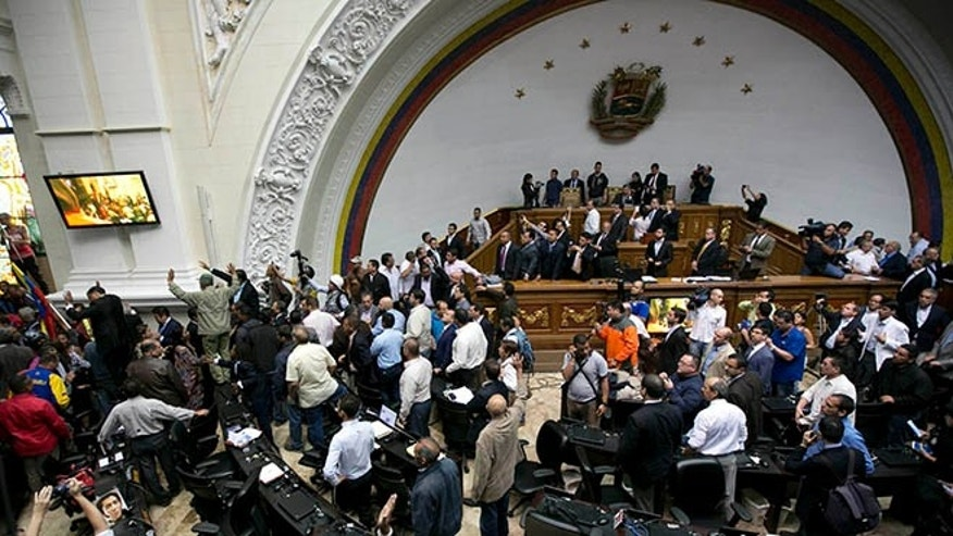 Lawmakers stand as a group of government supporters force their way into the National Assembly in Caracas, Sunday, Oct. 23, 2016.