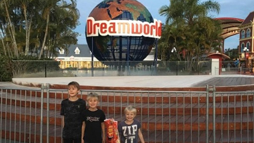 In this June 11, 2016 photo, children pose for a photo in front of the Dreamworld Globe on the Gold Coast, Queensland, Australia. Two men and two women died on Tuesday, Oct. 25, 2016, while on a river rapids ride at the popular theme park, officials said. A malfunction caused two people to be ejected from their raft, while two others were caught inside the ride, said Gavin Fuller, an officer with the Queensland Ambulance Service. (AP Photo/Grant McConachy)