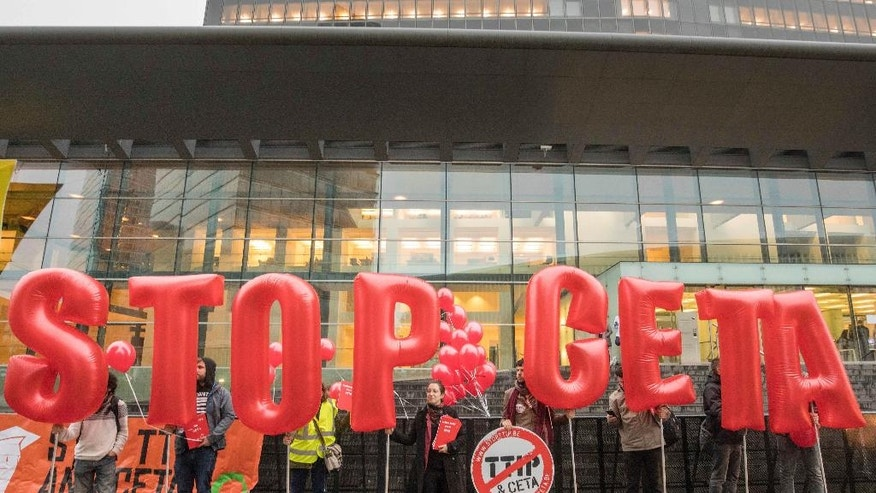 FILE - In this Tuesday, Oct. 18, 2016 file photo, protestors hold inflatable letters as they demonstrate outside a meeting of EU trade ministers at the EU Council building in Luxembourg. The small Belgian region of Wallonia is currently holding up the signature of a landmark free trade deal uniting over 500 million European Union citizens and 35 million Canadians. (AP Photo/Olivier Matthys, File)