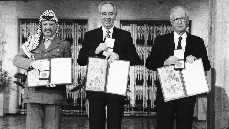 FILE - In this Dec. 10, 1994 file photo, PLO leader Yasser Arafat, left, Israeli Prime Minister Yitzhak Rabin, centre, and Israeli Foreign Minister Shimon Peres pose with their medals and diplomas, after receiving the 1994 Nobel Peace Prize in Oslo's City Hall. Nasser al-Qidweh, nephew of Yasser Arafat says the Hamas militant group has returned the late Palestinian leader's 1994 Nobel Peace Prize to the Palestinian government in the West Bank. al-Qidweh said Tuesday that the medal will be among dozens of Arafat's belongings to be displayed in a new museum opening in Ramallah on Nov. 9. Qidweh is president of the Arafat Institute. (AP Photo, File)