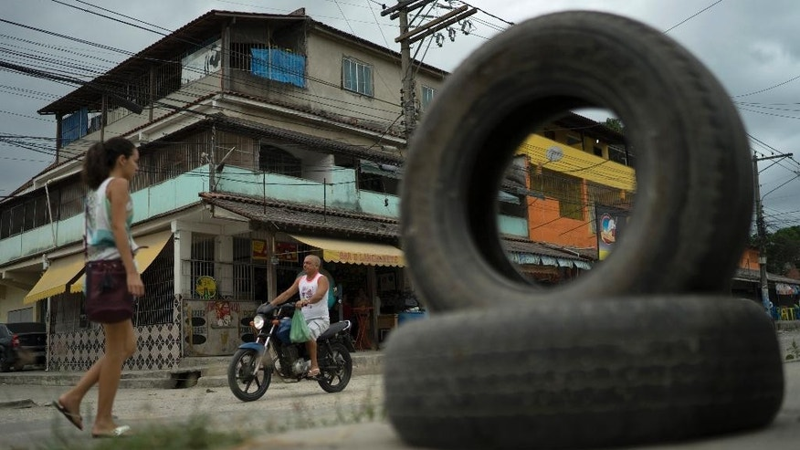 A man rides his motorcycle past the bar where a 34-year-old woman was attacked last week by suspected drug dealers in Sao Goncalo, Brazil, Tuesday, Oct. 25, 2016. The attack highlights the pervasive violence against women and girls in Latin America's largest nation just months after a 16-year-old girl was gang-raped. (AP Photo/Leo Correa)