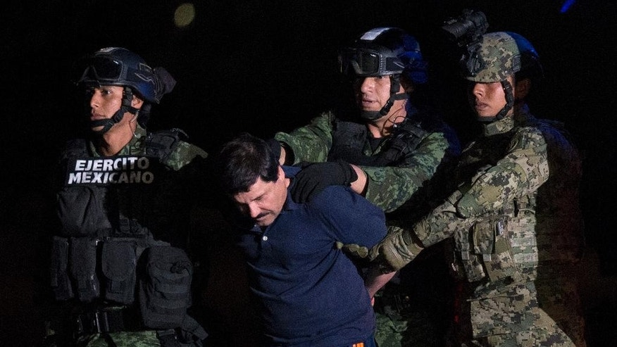 "FILE - In this Jan. 8, 2016 file photo, Mexican drug lord Joaquin ""El Chapo"" Guzman is escorted by army soldiers to a waiting helicopter, at a federal hangar in Mexico City. The common-law wife of imprisoned drug lord Joaquin ""El Chapo"" Guzman filed a complaint Monday, Oct. 24, 2016, with Mexico's National Human Rights Commission complaining of his treatment in prison. (AP Photo/Rebecca Blackwell, File)"