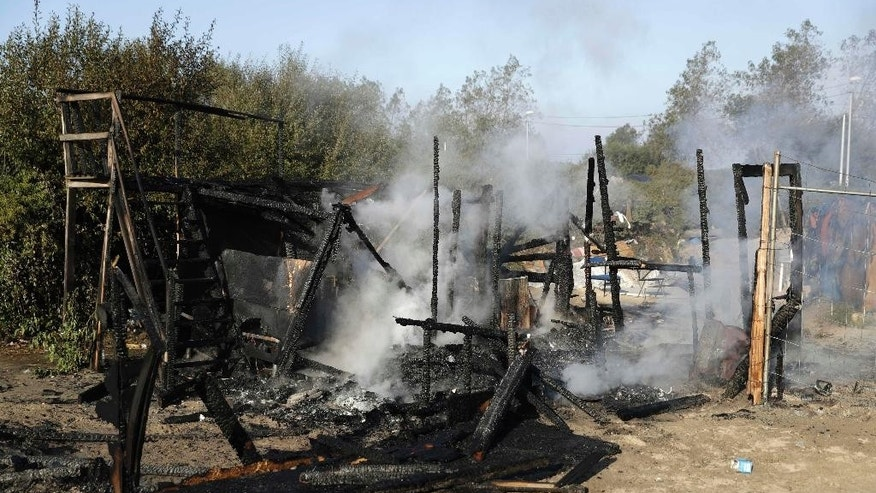 "The remains of a shelter that was set on fire Tuesday at the refugee camp known as ""The Jungle."""