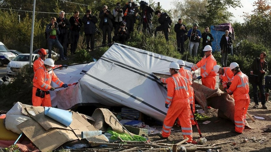 "Crews start to demolish shelters in the makeshift migrant camp known as ""the jungle"" near Calais, northern France, Tuesday, Oct. 25, 2016. Crews have started dismantling the migrant camp in France after the process to clear the camp began in earnest on Monday. (AP Photo/Thibault Camus)"