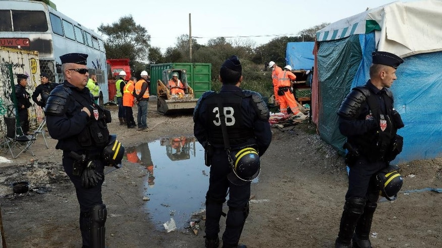 "Crews start to demolish shelters under the protection of riot police in the makeshift migrant camp known as ""the jungle"" near Calais, northern France, Tuesday, Oct. 25, 2016. Crews in hard hats and orange jumpsuits on Tuesday started dismantling a makeshift camp in France that has become a symbol of Europe's migrant crisis while thousands of people remained there waiting to be relocated. (AP Photo/Matt Dunham)"