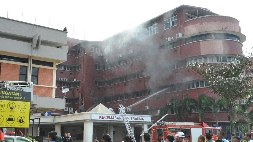 People watch firefighters putting out fire which broke out on the second floor of the Intensive Care Unit (ICU) of Hospital Sultanah Aminah in Johor Bahru in southern state of Johor, Malaysia, Tuesday, Oct. 25, 2016. The fire at the hospital has killed several patients and triggered the evacuation of hundreds of others. (AP Photo)