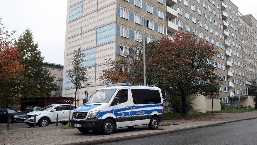 A police car stands in front of a building during a anti-terror operation  in Jena, eastern Germany, Tuesday Oct. 25, 2016.  German police say they searched apartments in five regions as part of an investigation into alleged involvement in terrorism by Chechen asylum seekers. (Bodo Schackow/dpa via AP)