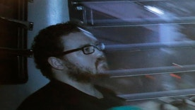 """FILE - In this Nov. 24, 2014 file photo taken through a tinted glass, Rurik Jutting, a British banker, sitting in a prison bus arrives at a court in Hong Kong.   A jury in Hong Kong watched chilling video Tuesday, Oct. 25, 2016,  of the British banker describing how he tortured and killed an Indonesian woman he met in a bar, saying he repeatedly raped her and """"tortured her badly.""""  In the video he shot, Jutting, a Cambridge University graduate on trial in Hong Kong's High Court for the murder of two Indonesian women, can be seen shirtless in his apartment. (AP Photo/Vincent Yu, File)"""