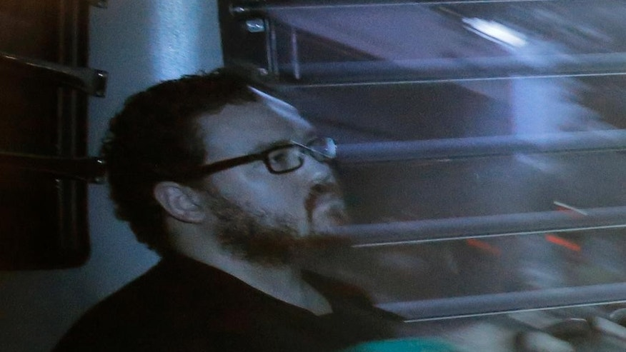 Rurik Jutting sitting in a prison bus in 2014.