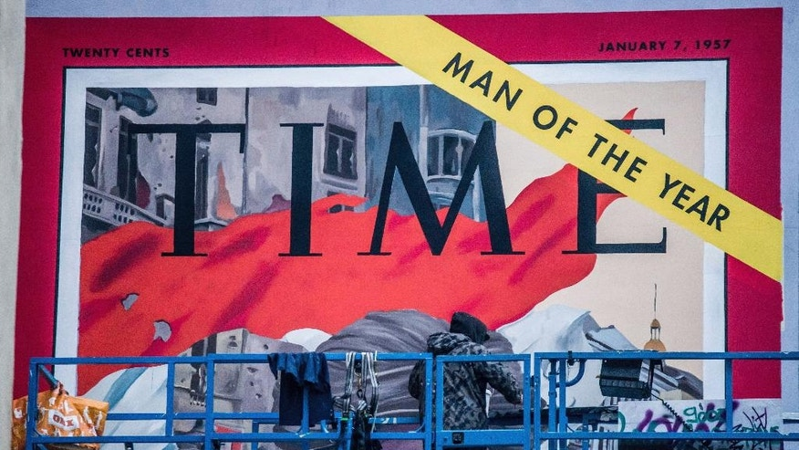 A mural duplicating the cover of the Jan. 7, 1957 issue of the US Time magazine is applied on a building by a street artist of the legal graffiti organization, Szines Varos (Colourful City) to mark the 60th anniversary of the outbreak of the 1956 Hungarian revolution and freedom fight in Budapest, Hungary, Sunday, Oct. 23, 2016. The magazine cover featured Hungarian civilians who participated in the fights against communism and Soviet rule. (Zoltan Balogh/MTI via AP)