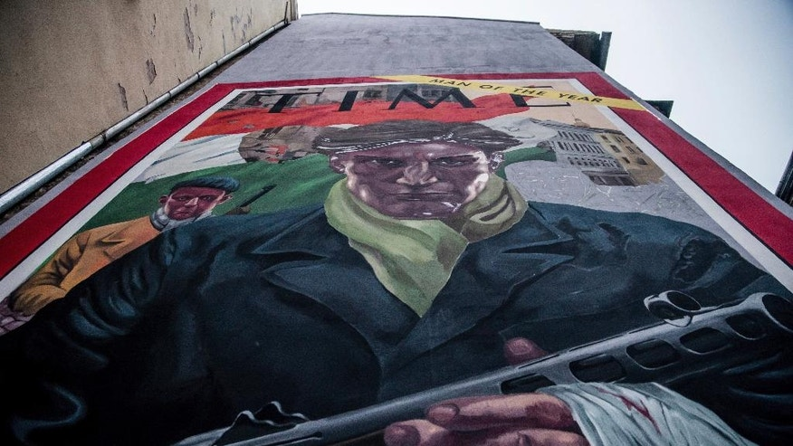 A mural duplicating the cover of the 7 January 1957 issue of the US Time magazine is depicted on a building to mark the 60th anniversary of the outbreak of the 1956 Hungarian revolution and freedom fight in Budapest, Hungary, Sunday, Oct. 23, 2016. The magazine cover featured Hungarian civilians who participated in the fights against communism and Soviet rule. (Zoltan Balogh/MTI via AP)