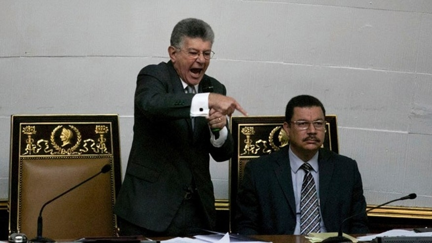 "Congressional President Henry Ramos Allup, left center, gives a speech during a special session of Congress in Caracas, Venezuela, Tuesday, Oct. 25, 2016. After the government suspended a recall referendum seeking the president's removal last week, the opposition-controlled congress began debating Venezuelan President Nicolas Maduro's ""constitutional situation."" Lawmakers vow to present evidence that he's a dual Colombian citizen and therefore constitutionally ineligible to hold Venezuela's highest office. (AP Photo/Alejandro Cegarra)"